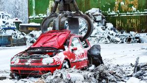 Valokuvassa punainen auto romuttamolla.