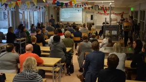 En skolmatsal där man ser ryggarna på många föräldrar som lyssnar på en man längst framme.