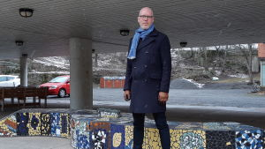 man i fyrtioårs-åldern står bredbent på skolgård med ljusblå halsduk och mörkblåa kläder