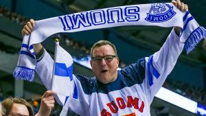 En supporter håller i en flagga med texten Finland.