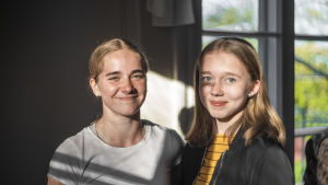 Två unga kvinnor ser in i kameran. De är inne i ett hus. Solen lyser in på deras ansikte. De ser glada ut.
