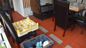 Glas, muggar och andra kärl i stora plastlådor på ett golv.