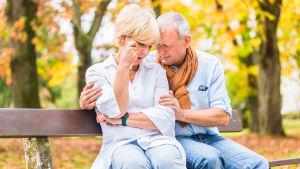 en äldre kvinna och äldre man sitter på en parkbänk. Kvinnan gråter och mannen tröstar henne.