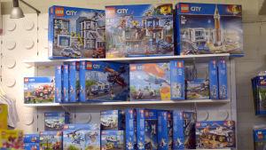 Legoleksakslådor är uppstaplade på en grupp hyllor.