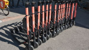 Röda elsparkcyklar står på rad på en gata.