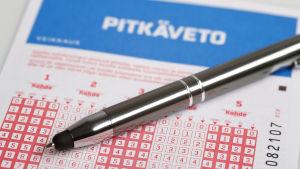 En spelkupong ligger under en penna.