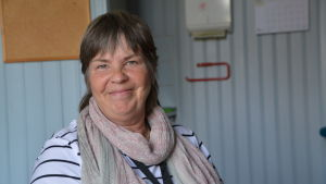 Kvinna ler i ett lärarum med ljusblåa träväggar.