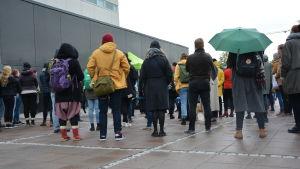 En grupp med människor har samlats utanför en byggnad och står med ryggen mot kameran.