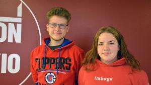 Två gymnasieelever i röda tröjor står bredvid varandra, framför en röd vägg.