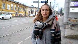 En kvinna står vid sidan av vägen inne i en stad.