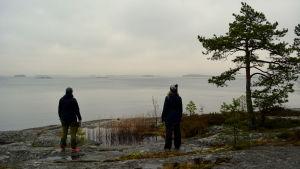 Sarah Grönstrand och Johanna Sandin står på klipporna med ryggen åt och tittar ut mot dimmigt hav.
