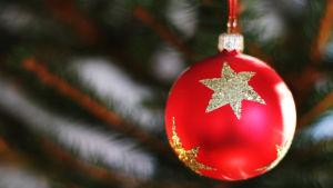 en röd julgransboll som hänger i julgranen