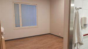 Ett rum med ljust golv och vita vägger. Toaletten skymtar till höger,