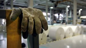 Ett par handskar hängda över ett räcke syns i förgrunden. I bakgrunden ser man en pappersfabrik.