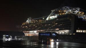 Buss framför kryssningsfartyget Diamond Princess i hamnen i Yokohama, Japan. Bilden är tagen på kvällen så det är mörkt på bilden.