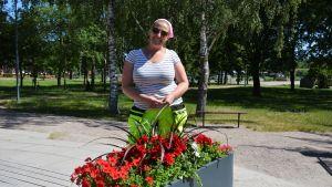 Jessica Engroos framför en blomrabatt