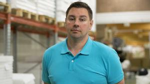 En man i blå pikeskjorta som står i ett fabriksutrymme.