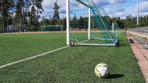 En fotboll bredvid ett mål på en fotbollsplan.
