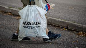 En person bär på en plastpåse full med mat. Endast skorna och plastpåsen syns i bild.