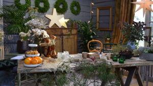 En del av ett rum som är pyntat i gröna och vita juldekorationer. På bordet finns olika pysselmaterial som torkade blommor, torkade apelsinskivor, olika juteband och snören, torkat gräs.