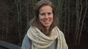 En leende kvinna med sjal.