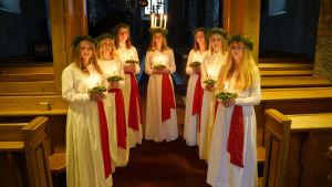 Lucia med sex tärnor inne i en kyrka.
