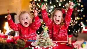 Två barn sitter i röda jultröjor vid ett bord. De sträcker på händerna och ser glada ut.