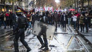 Två poliser med hjälm sköld går på en våt gata framför en folkmassa med banderoller och paraplyer.