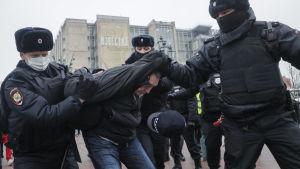Polisen för bort en manlig demonstrant. I bilden håller de hans händer bakom ryggen och drar honom framåt genom att hålla i hans rock.