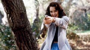 Veronica (Winona Ryder) sihtailee pistoolilla kohti kameraa suu naurussa elokuvassa Heathers.