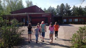 Elever och rektor går mot skolbyggnaden.