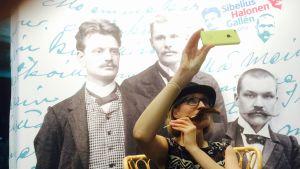 Marjut Tervola poseeraa suurmiesten seurassa