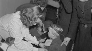 Finska krigsbarn på väg till Svrige får en lapp runt halsen inför resan i Viiborg år 1944
