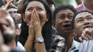 Anhängare av Aung San Suu Kyis parti NLD reagerar med glädje då de ser på den pågående rösträkningen i Rangoon, Burma.