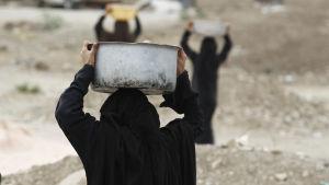 Kvinna i Jemen transporterar vattenkärl