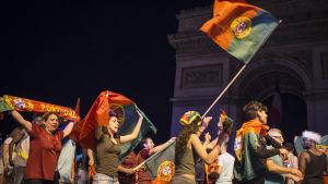 Portugisiska fotbollsfans firar segern  genom att vifta med och klä sig i den portugisiska rödgröna flaggan på Chapms-Elysees i Paris.