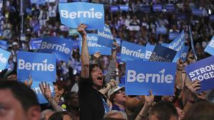 Delegater vid demokraternas partikonvent viftar med Bernie-skyltar