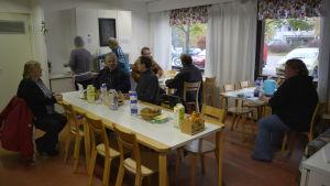 Åtta personer i en matsal. Sex personer sitter vid tre olika bord. Två andra står i bakgrunden och tar mat. Det finns bröd, mjölk, vatten och kryddor på borden.