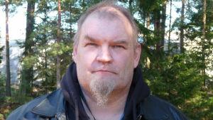 porträtt på Thomas Salin, taget utomhus med granar och tallar i bakgrunden