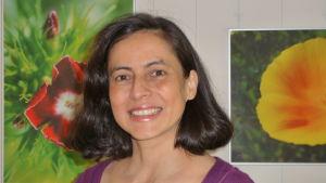 Luz Angela Lopez med två blomtavlor i bakgrunden.