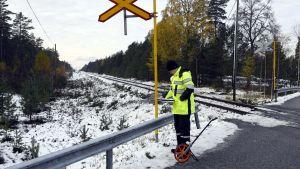 En anställd vid Olycksutredningscentralen undersöker platsen för storolyckan vid en plankorsning i Raseborg.