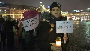 Kvinna håller plakat med texten stopp min kropp och ett tänt ljus under me too- demonstration i Åbo.