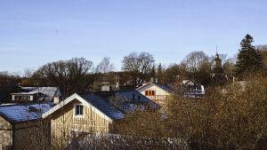Puutalojen kattoja, taustalla kirkon torni, puissa ei lehtiä, kuva otettu talvella.