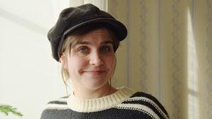 En bild på en kvinna i hatt och tröja.