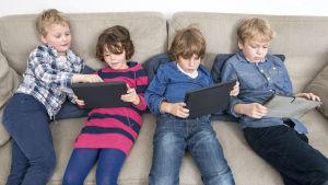 Barn sitter i en soffa och tittar och spelar på sina pekplattor.