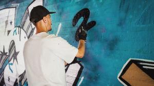 Janne Saarikoski i full fart med att spraymåla en vägg.