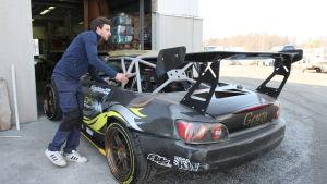 Dennis Häggblom rullar ut den specialbyggda tävlingsbilen ur verkstaden.