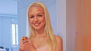 en ung flicka med en hamster i famnen