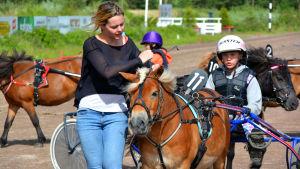 Malin Kullberg justerar remmarna på ponnyn
