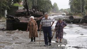 Lokalinvånare går förbi en förstörd Georgisk pansarvagn.